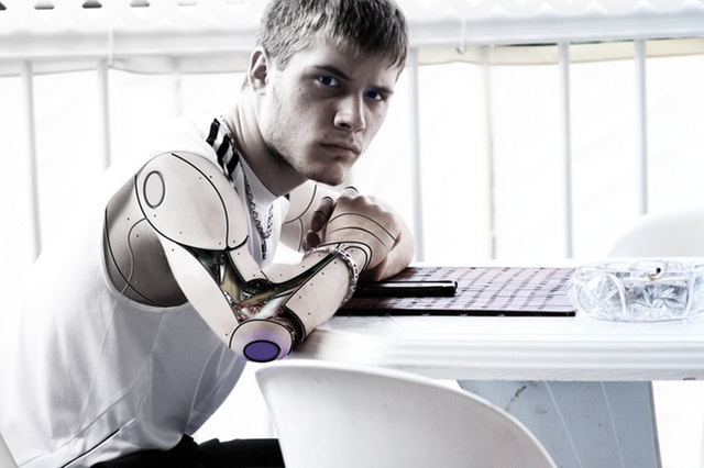 Man with steel artificial arm sitting in front of laptop