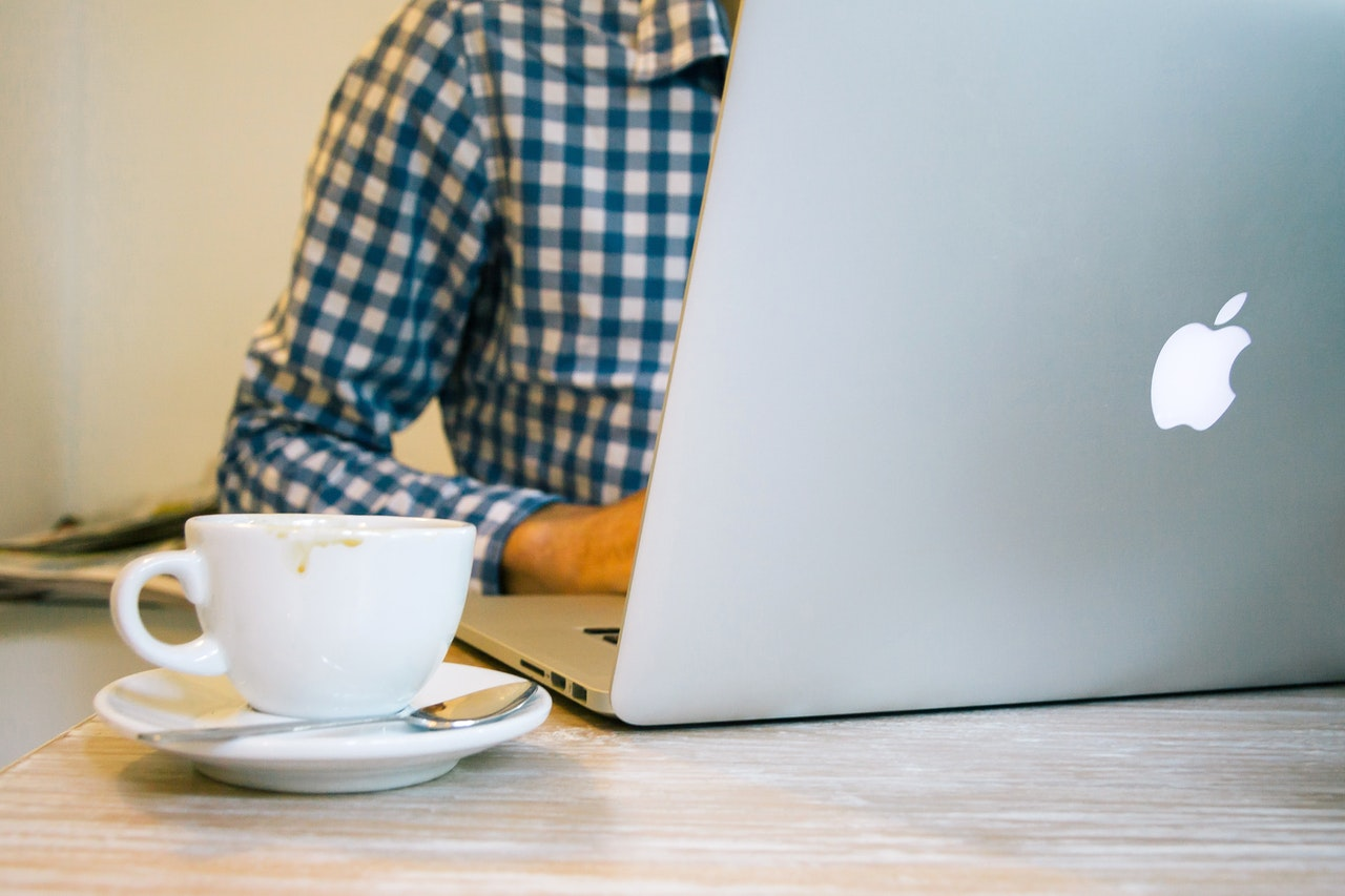A man sitting at a laptop with a coffee cup beside him