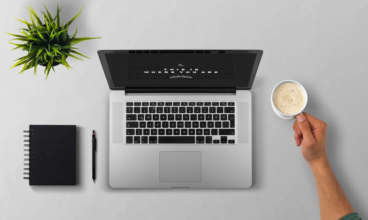 A birds-eye view of an open laptop with a plant and notebook to the left, and a person holding a coffee mug to the right
