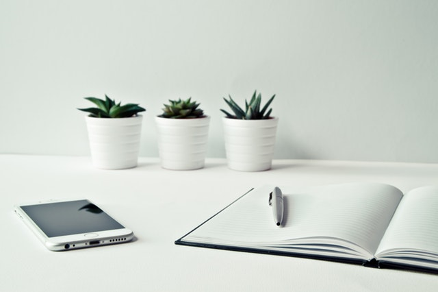 Three white ceramic pots with succulents in each one near an open notebook and a mobile phone