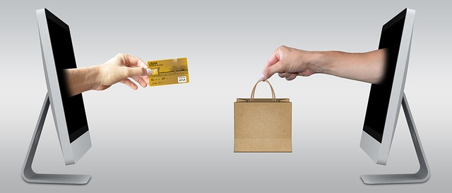 Two computer screens facing each other, one with a hand holding a credit card, the other with a hand holding a paper bag