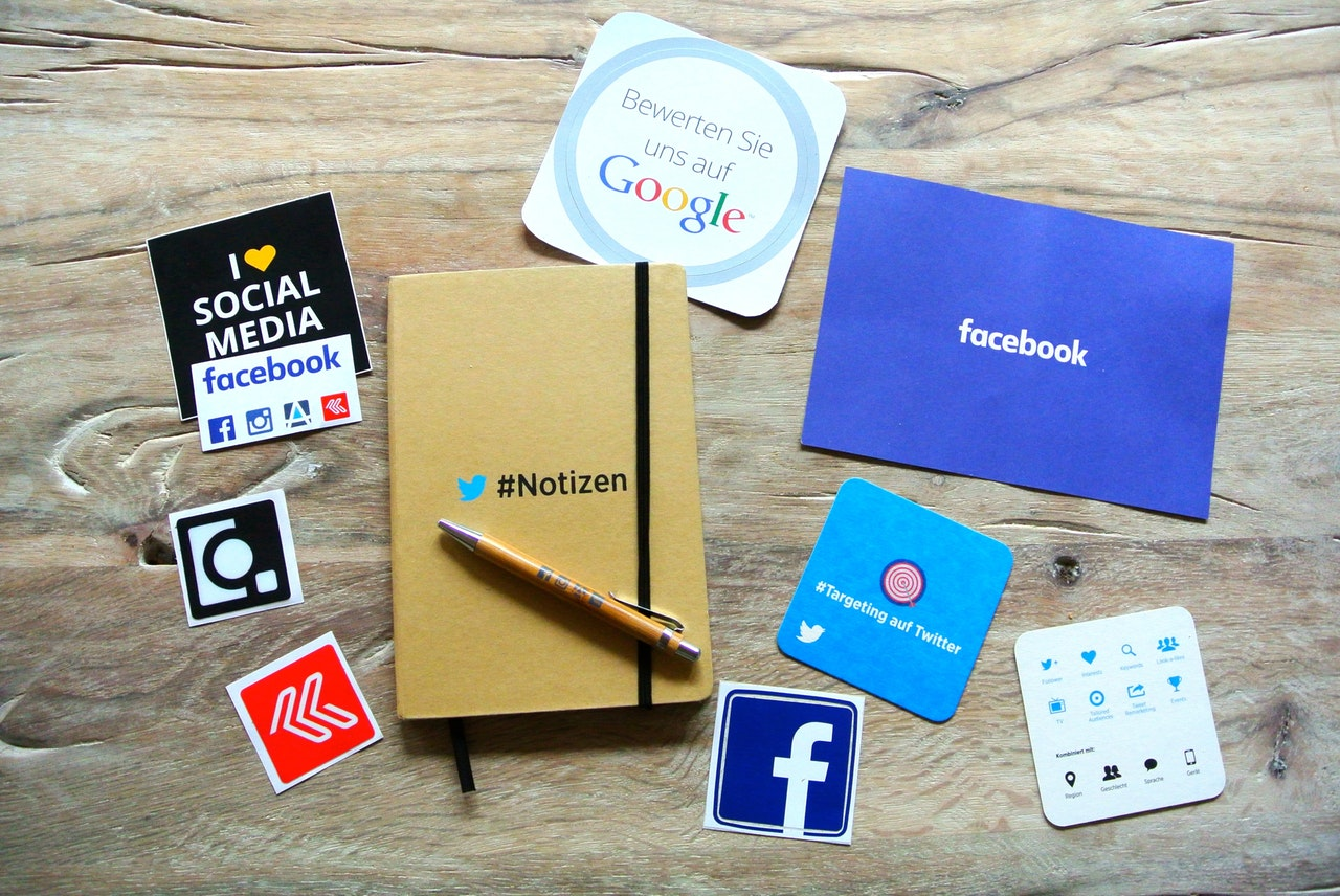 A wooden table with various social media related items on it including 2 coasters, stickers and a Twitter notebook and pen