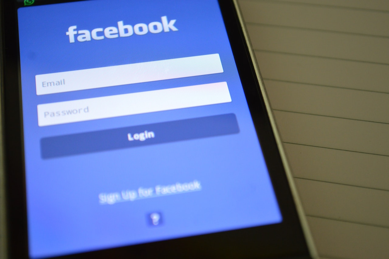 A close up of a mobile phone opened to the Facebook app before you log in. The screen is blue with the word Facebook writtern at the top.