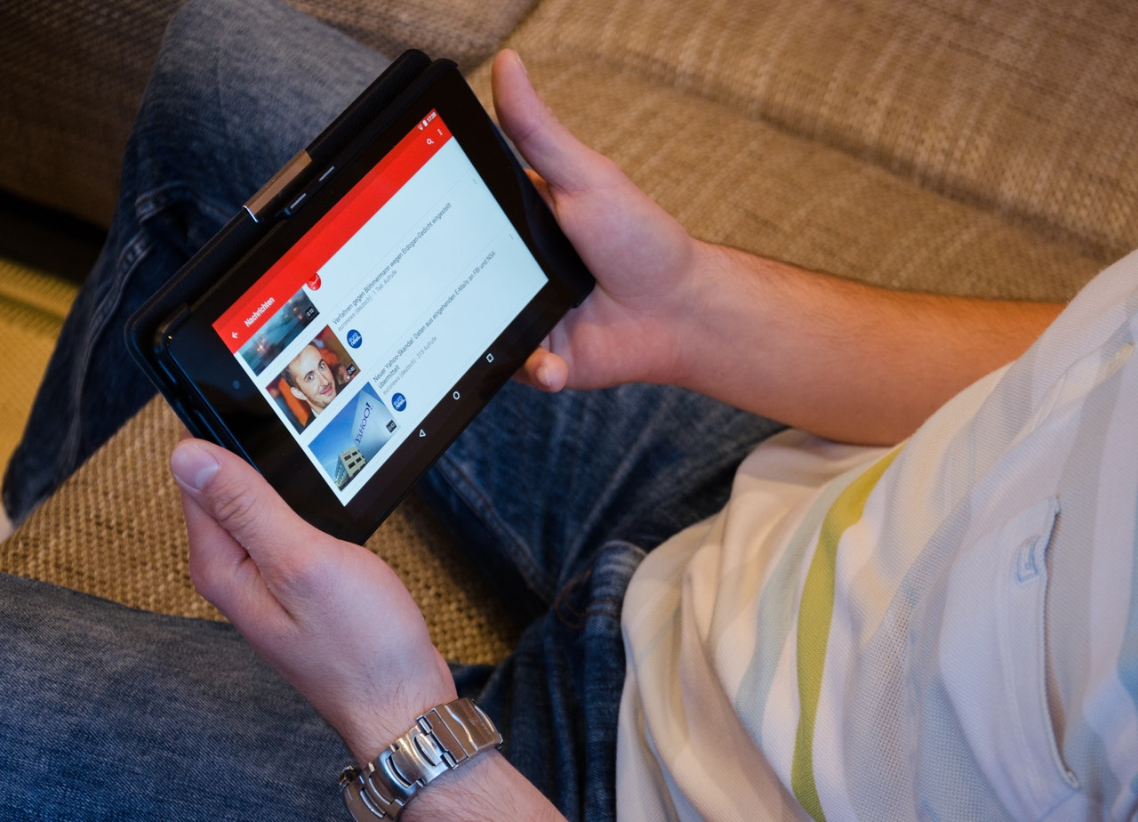 A man holding a tablet to the YouTube app